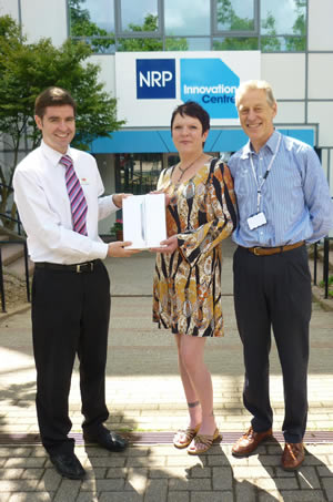 James Beaves, Thermo Fisher Scientific (left), presents Amy Fox (centre) with her iPad, accompanied by Paul Dexter, Head of Bacteriology (right).